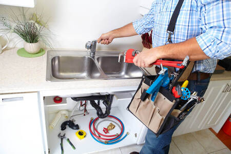 A handyman Mandurah worker fixing a leaking sink tap with a tool belt on and his tool laid out around the sink floor