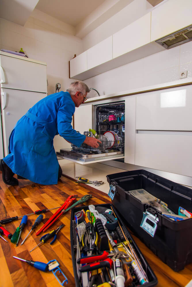 A senior handyman Mandurah worker fixing a broken dishwasher in blue overalls with his toolbox open next to the dishwasher full of tools