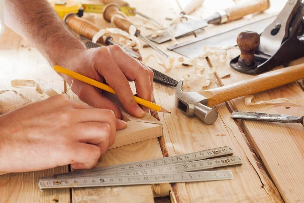 close up image of a handyman Mandurah worker putting together the corner of a picture frame with wood shavings everywhere and some tools close by