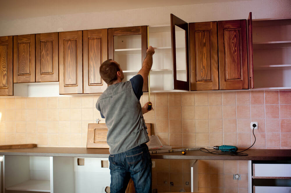 A handyman Mandurah worker installing some new dark brown kitchen cabinets whilst checking a measurement with a tape measure
