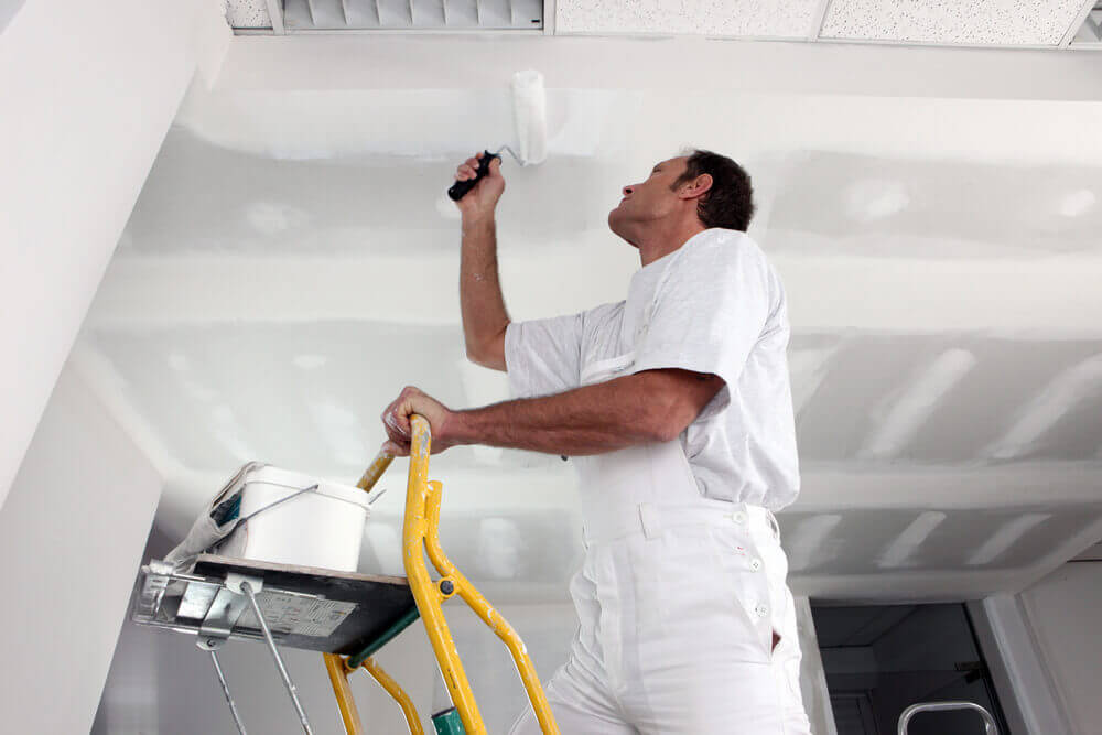A handyman Mandurah worker in some white overalls painting a ceiling on a ladder with a paint roller